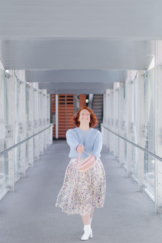 Sur la passerelle de Poitiers en train de marcher, les cheveux au vent en tenue pastel, jupe qui tourne et pull court