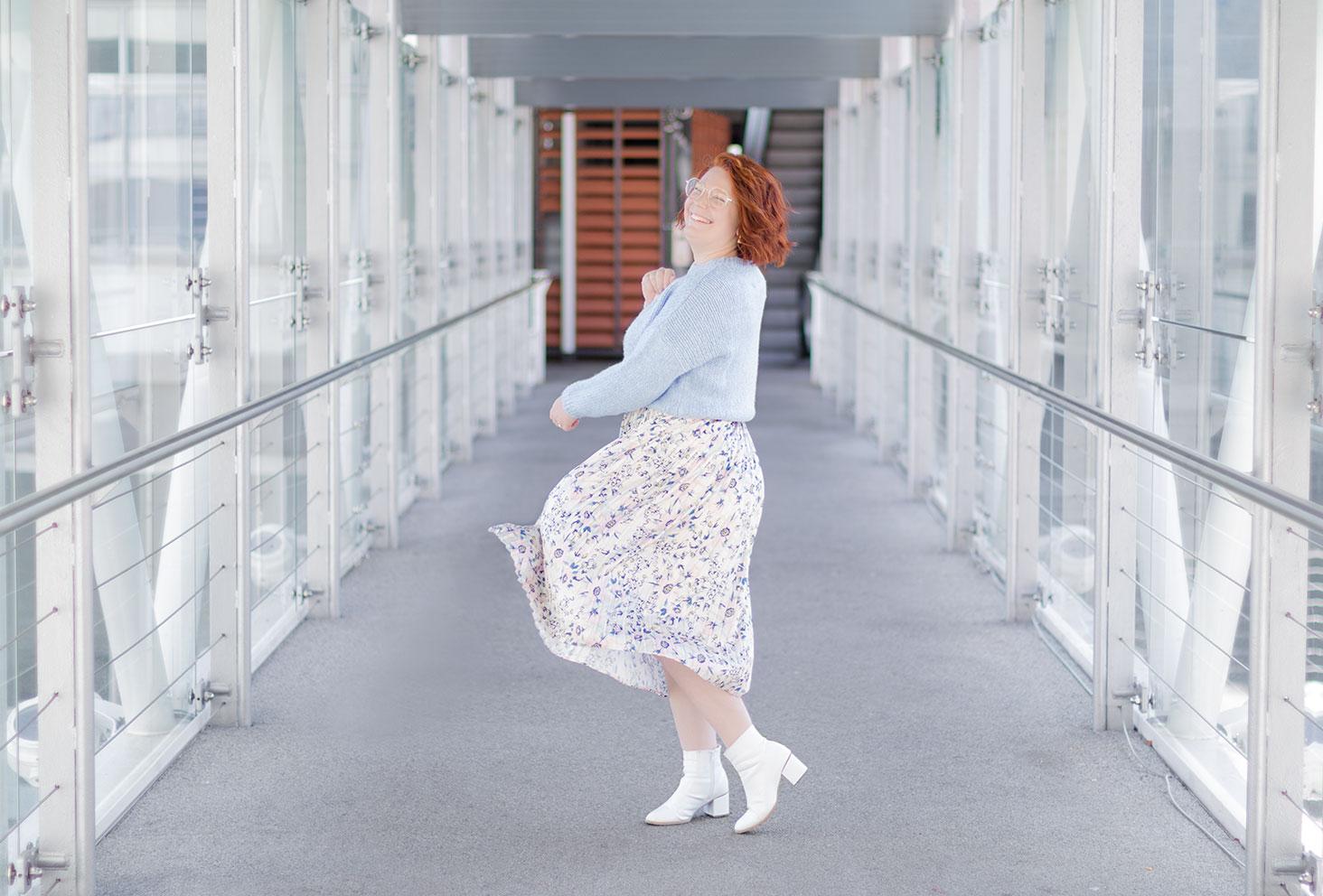 Sur une passerelle au-dessus d'une route, en robe qui tourne pastel et bottines blanches, avec le sourire