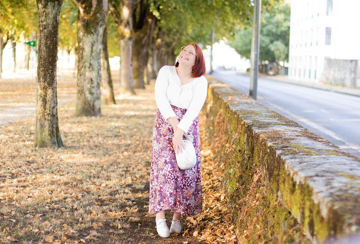 Dans un décor d'automne, en jupe longue rose à fleurs et pull blanc, avec le sourire
