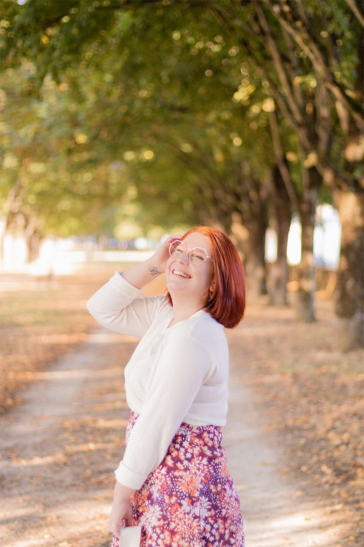 Portrait en pull blanc et de profil, avec le sourire, une main dans les cheveux