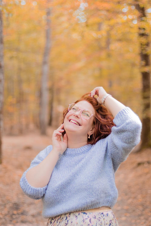 Avec le sourire au milieu des bois zoom sur le pull bleu pastel porté, avec le sourire et les mains dans les cheveux