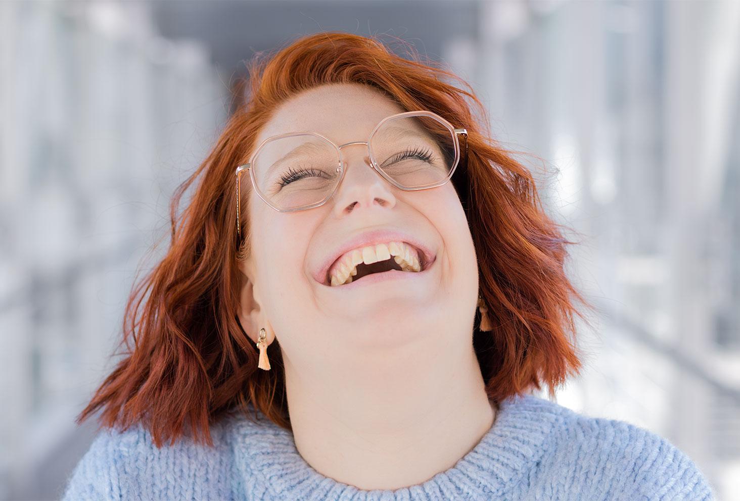 Portrait zoomé avec le sourire jusqu'aux oreilles et les cheveux ondulés