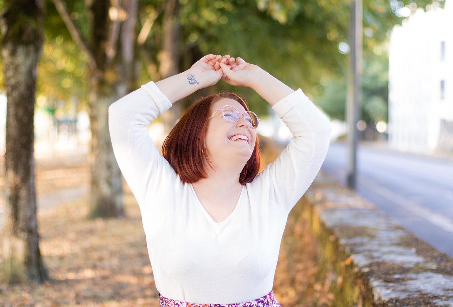 Zoom sur le pull blanc porté dans un décor d'automne avec le sourire
