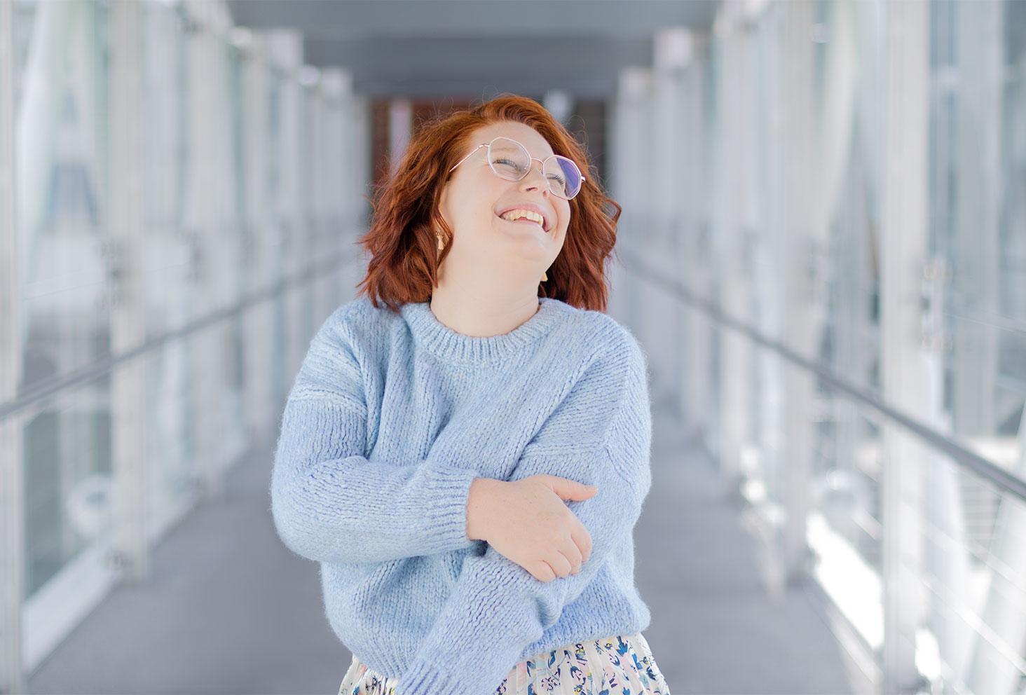 Zoom sur le pull bleu clair court porté, avec le sourire et une main sur l'autre bras