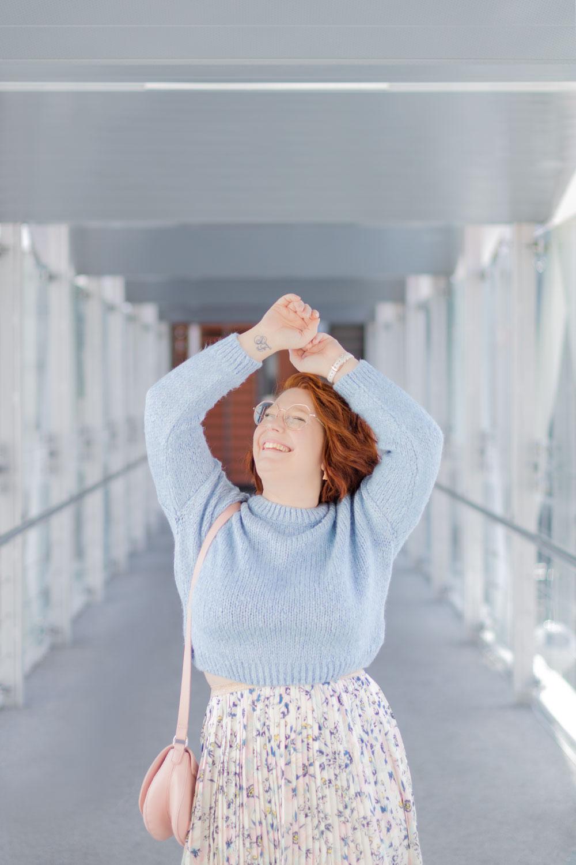 Zoom sur le pull bleu clair court porté avec une jupe fluide, les bras au-dessus de la tête avec le sourire
