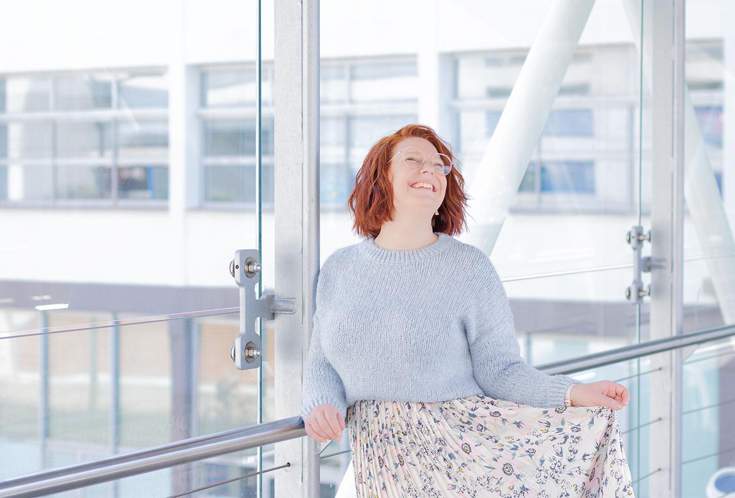 Zoom sur le pull court bleu clair porté avec une jupe pastel, appuyée le long des vitres d'une passerelle, avec le sourire