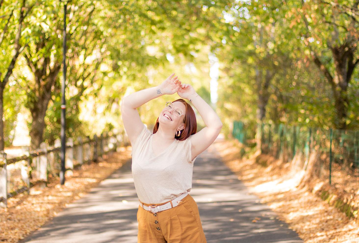 Les bras levés au dessus de la tête avec le sourire, en t-shirt beige, au milieu d'une rue d'automne