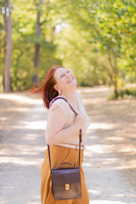 Zoom sur le sac vintage marron en cuir Le Tanneur, porté avec un t-shirt beige et un pantalon camel, de profil avec le sourire et les cheveux dans le vent