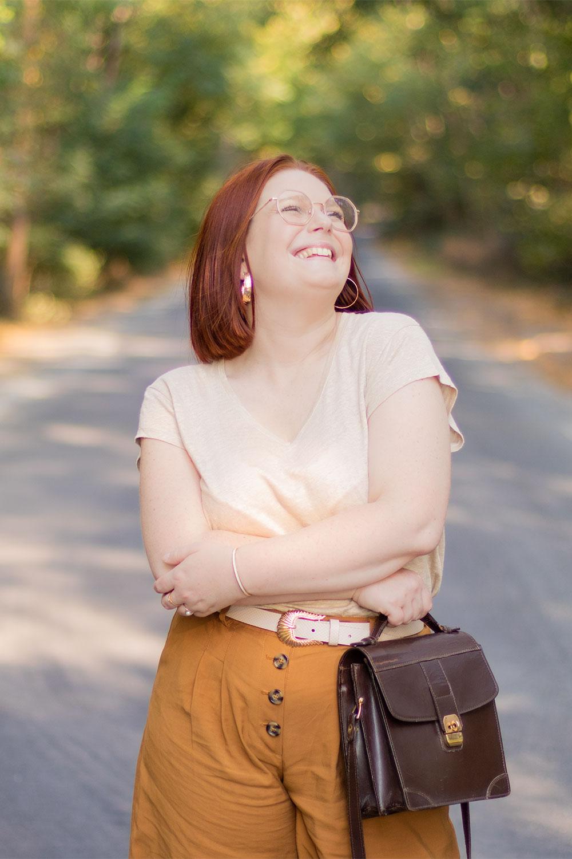 Dans une grande rue de Montlouis en t-shirt en lin beige, avec le sourire, un sac vintage marron en cuir dans la main
