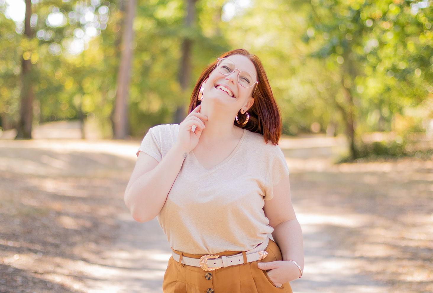 Zoom sur le t-shirt beige en lin porté, avec le sourire et une main dans le cou, les cheveux dans le vent