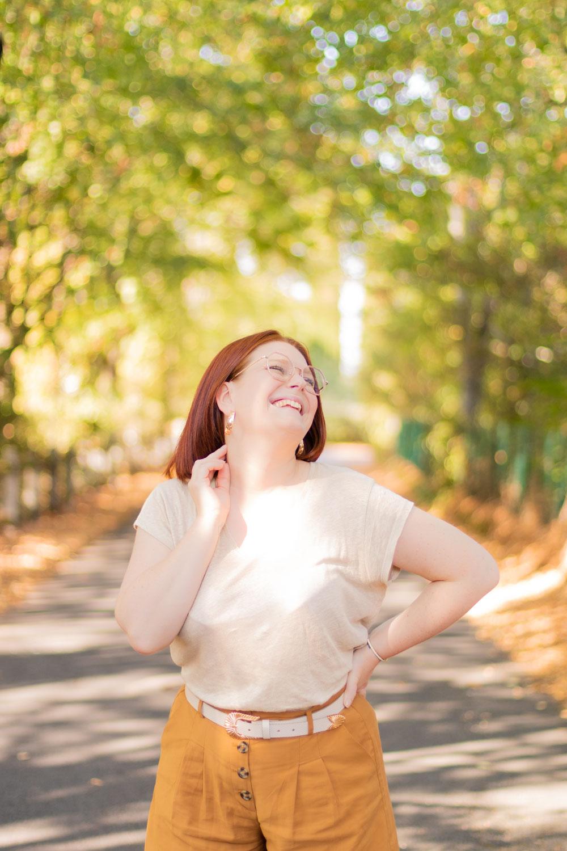 En t-shirt lin en beige en pantalon camel, avec le sourire et une main dans le cou, avec le sourire