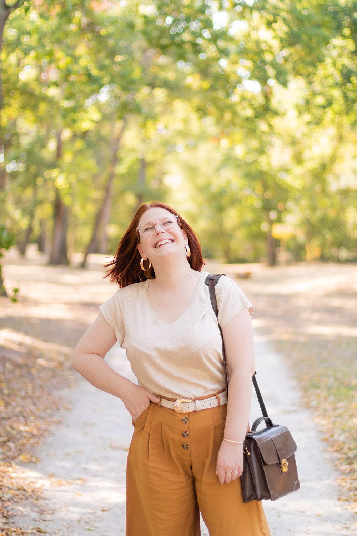 Avec le sourire et un main dans la poche, au milieu d'un parc boisé, en t-shirt en lin et pantalon loose camel