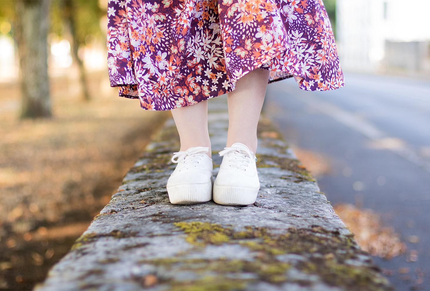 Zoom sur les baskets blanches Victoria portées avec une jupe longue rose, debout sur un mur en pierre