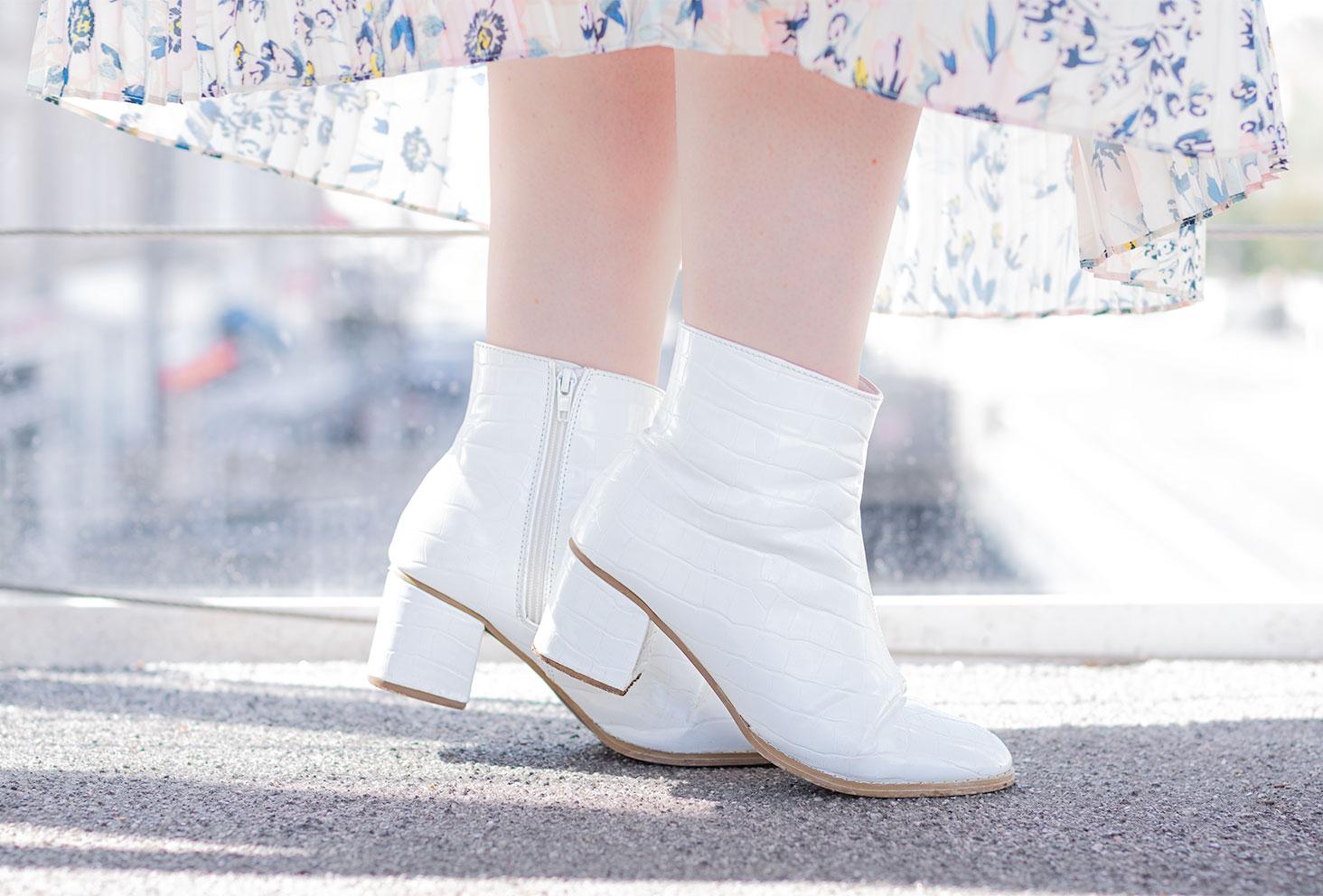Zoom sur les bottines blanches à talons effet croco portée avec une jupe longue qui vole