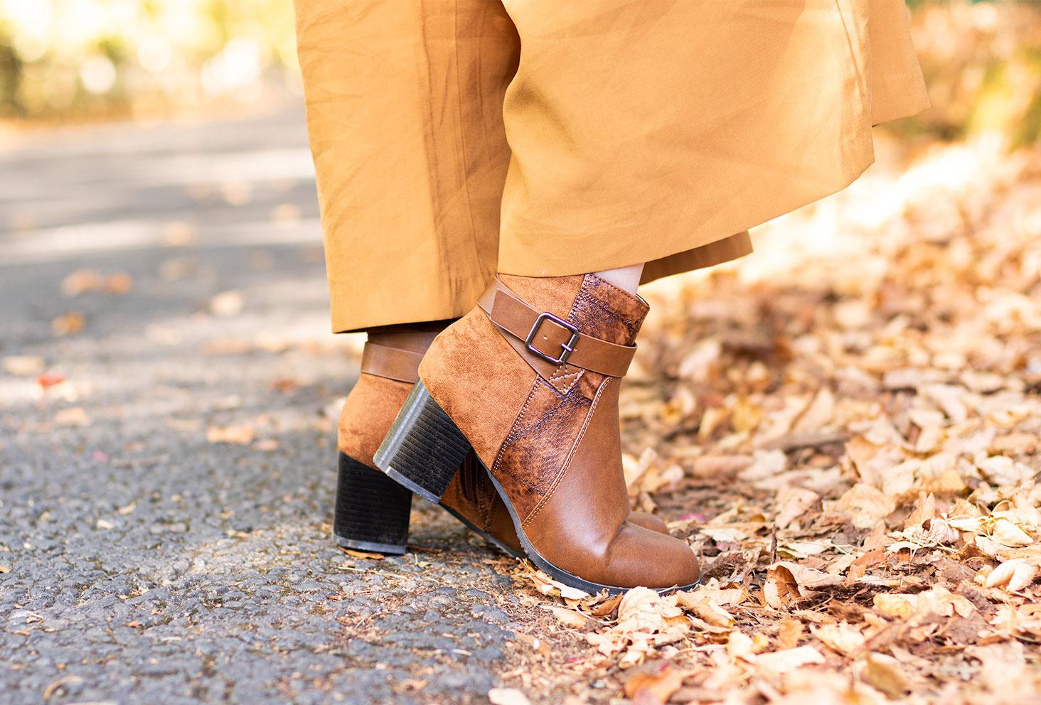 Zoom sur les bottines marrons Bréal porté avec un pantalon large camel, un pied sur la route et l'autre pied dans les feuilles mortes automnales