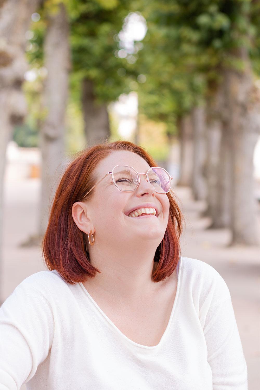 Portrait en pull blanc avec le sourire et des lunettes hexagonale sur le nez