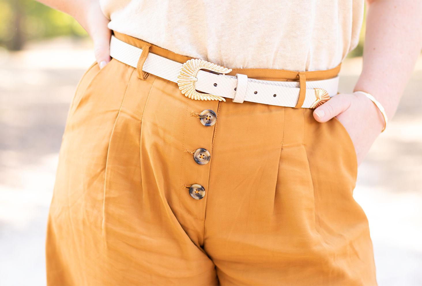 Zoom sur la ceinture beige effet croco porté sur un pantalon camel, un t-shirt beige fluide rentré dans le pantalon