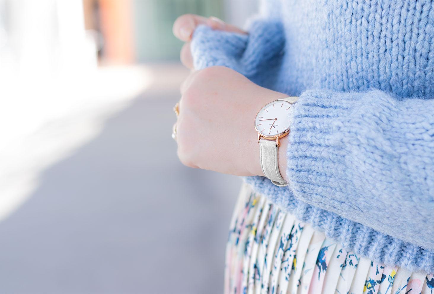 Zoom sur la montre blanche Daniel Wellington portée avec un pull en laine bleu clair