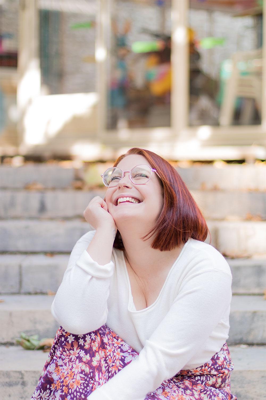 Assise dans les marches avec le sourire, un pull léger blanc sur le dos