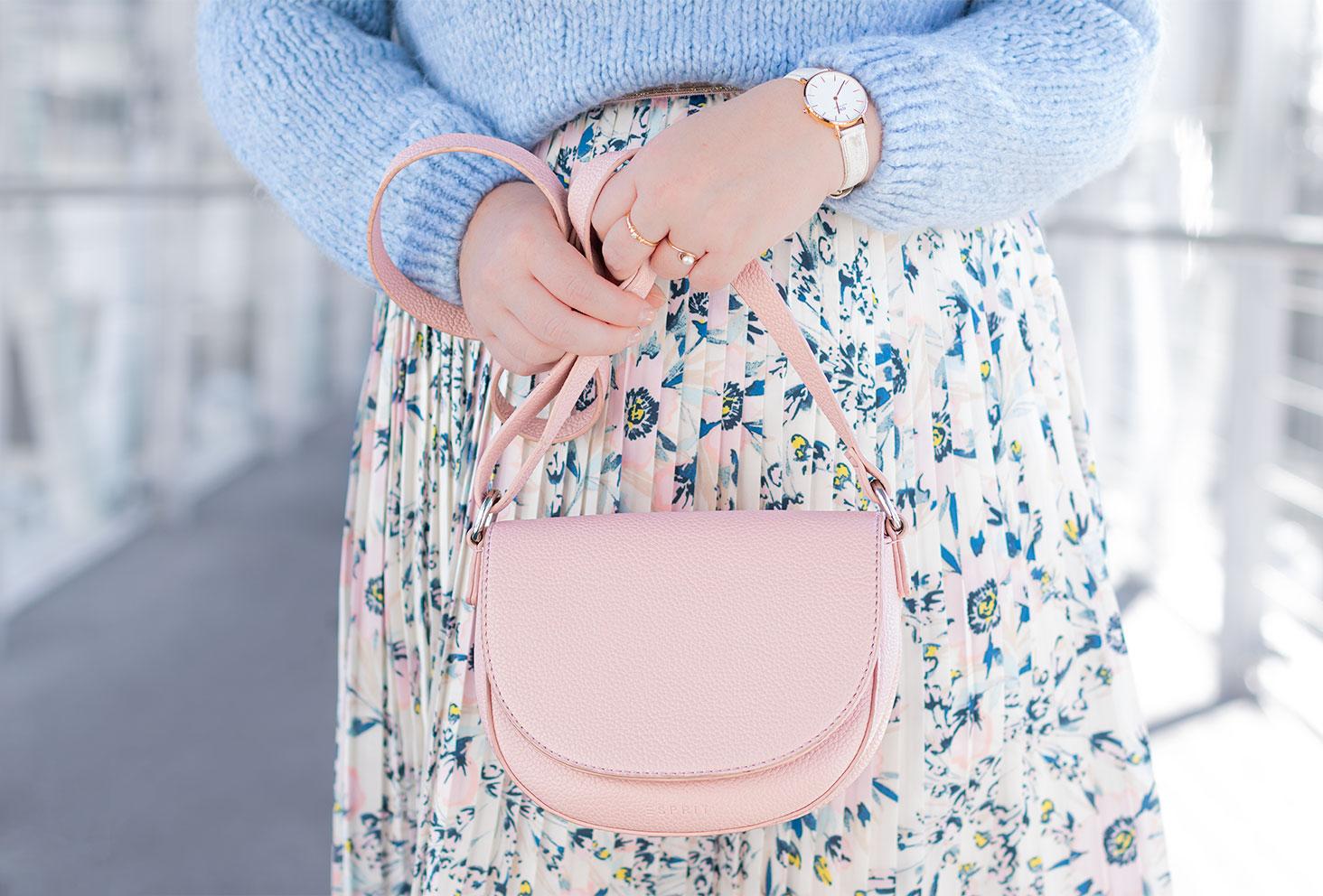 Zoom sur le sac rose à bandoulière tenu entre les mains devant une jupe aux couleurs et motifs pastels