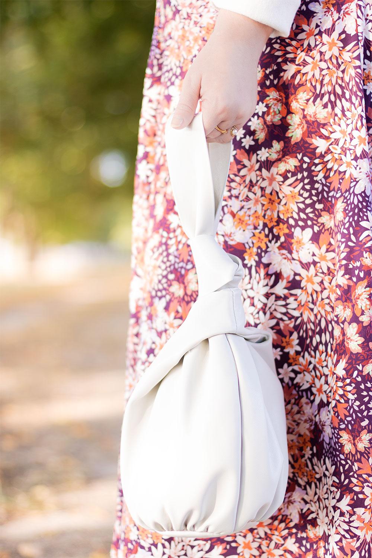 Zoom sur le sac sceau blanc Mango porté avec une jupe rose