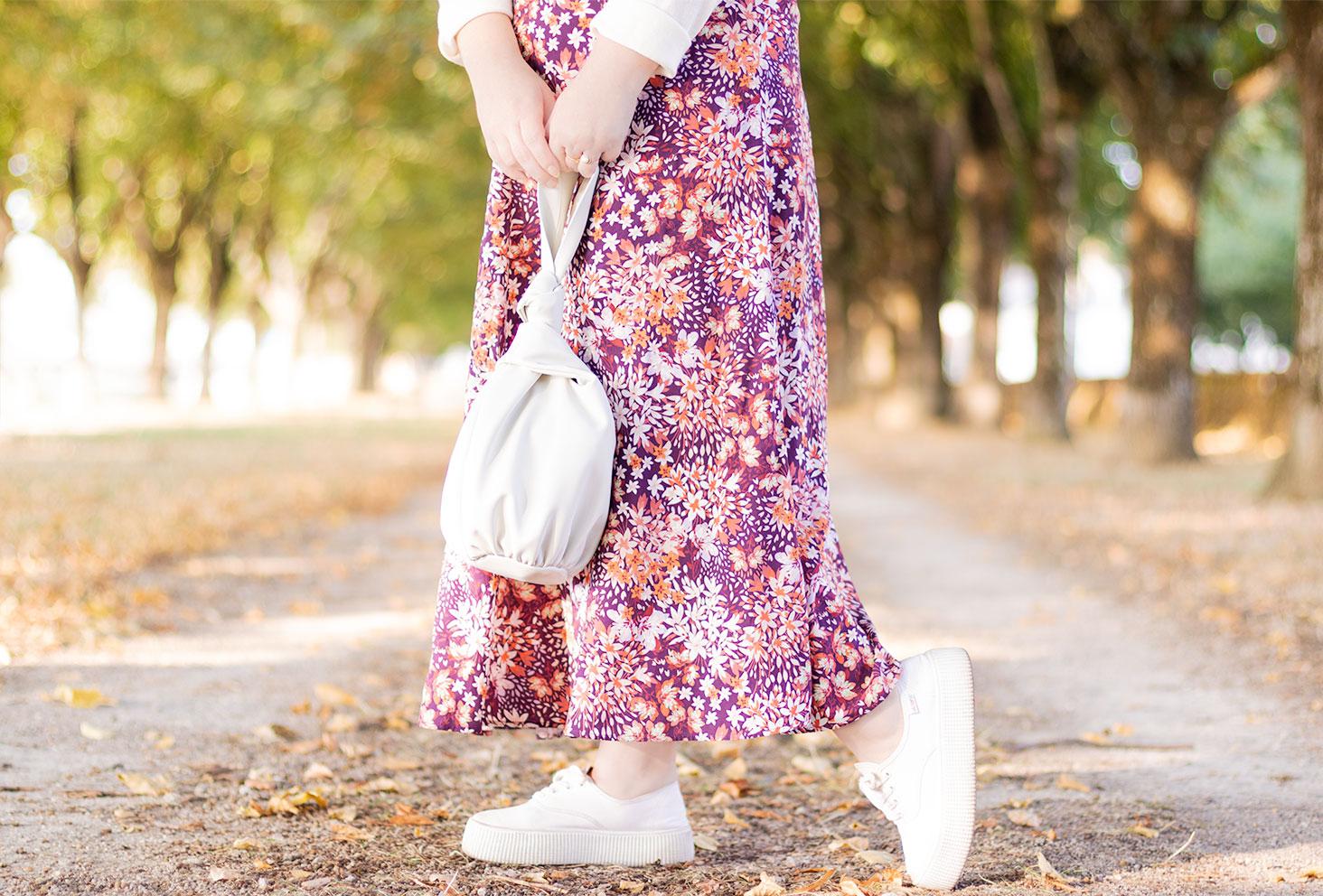 Zoom sur le sac sceau blanc Mango et les baskets à plateformes Victoria portés avec une jupe longue rose et violette