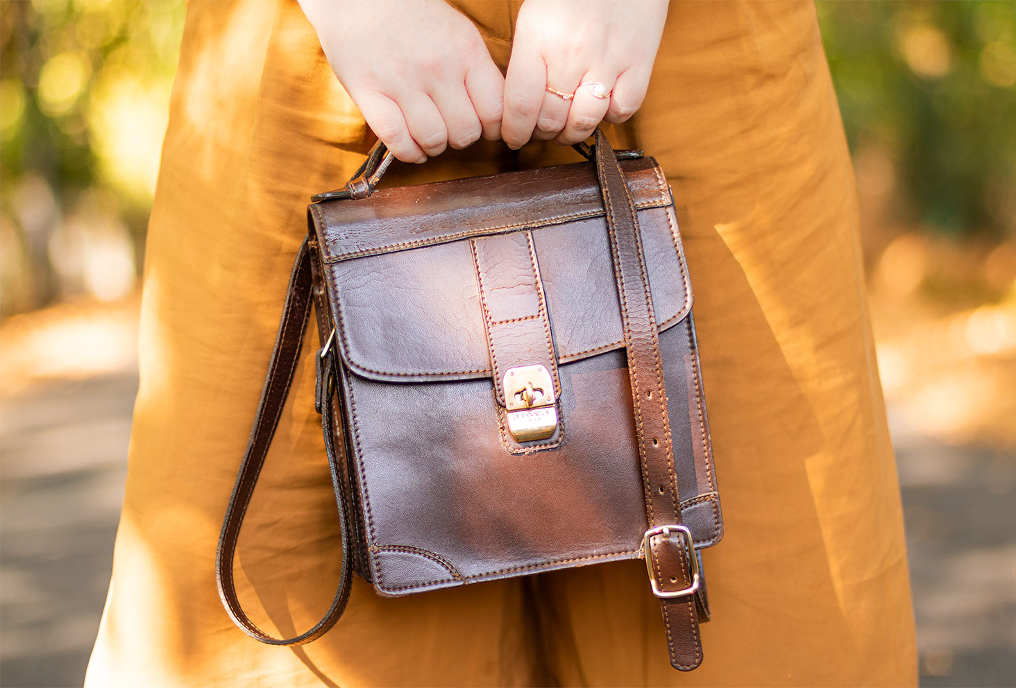 Zoom sur le sac vintage marron Le Tanneur, chiné en vide grenier, tenu dans les mains devant un pantalon camel