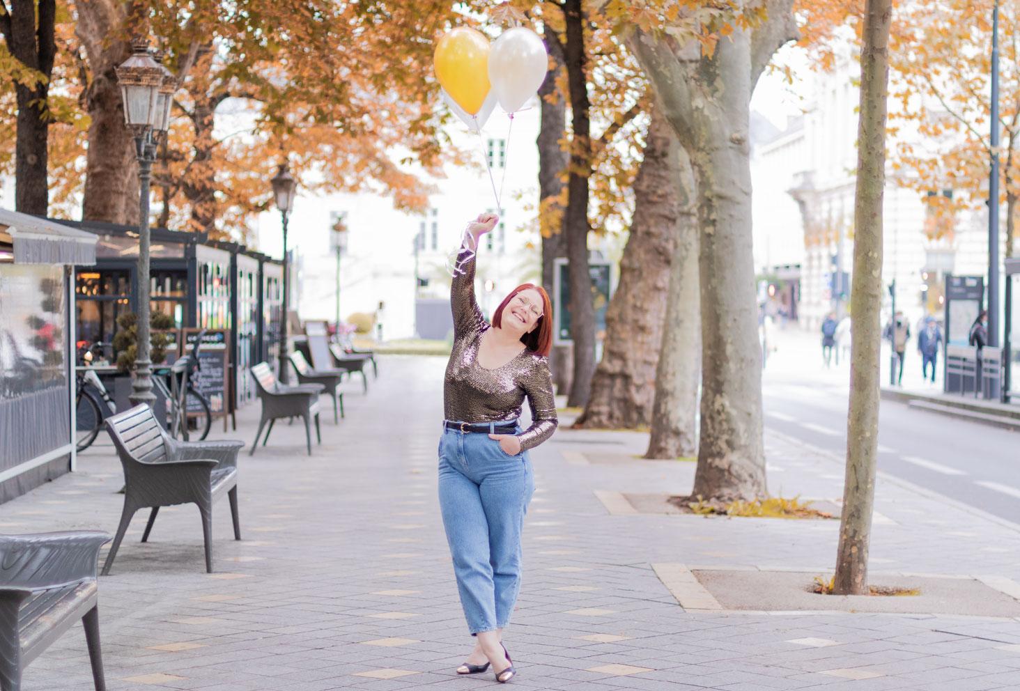 Dans la rue avec des ballons dorés, en body pailleté et jean, avec le sourire