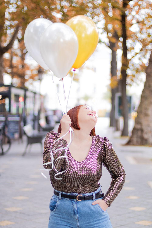 Photo avec des ballons dorés dans les mains, en body à paillette, avec le sourire en centre ville