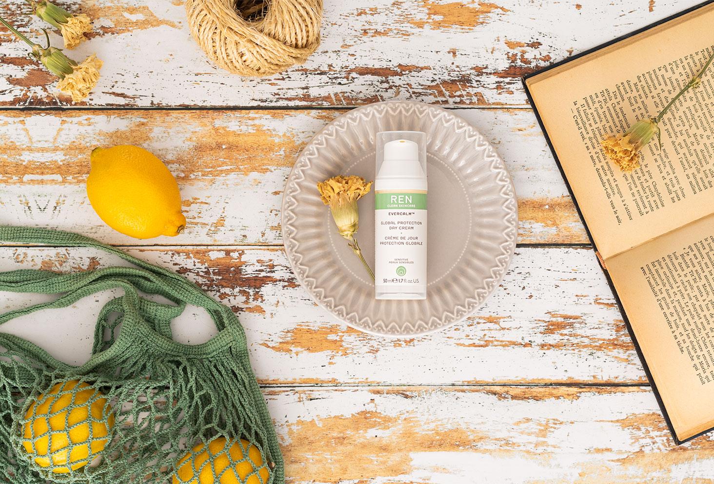 La crème de jour protection globale de Ren posée dans une assiette à côté d'un livre ancien et de citron