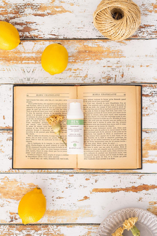La crème hydratante de jour de Ren posée sur un livre ancien ouvert au milieu de citrons