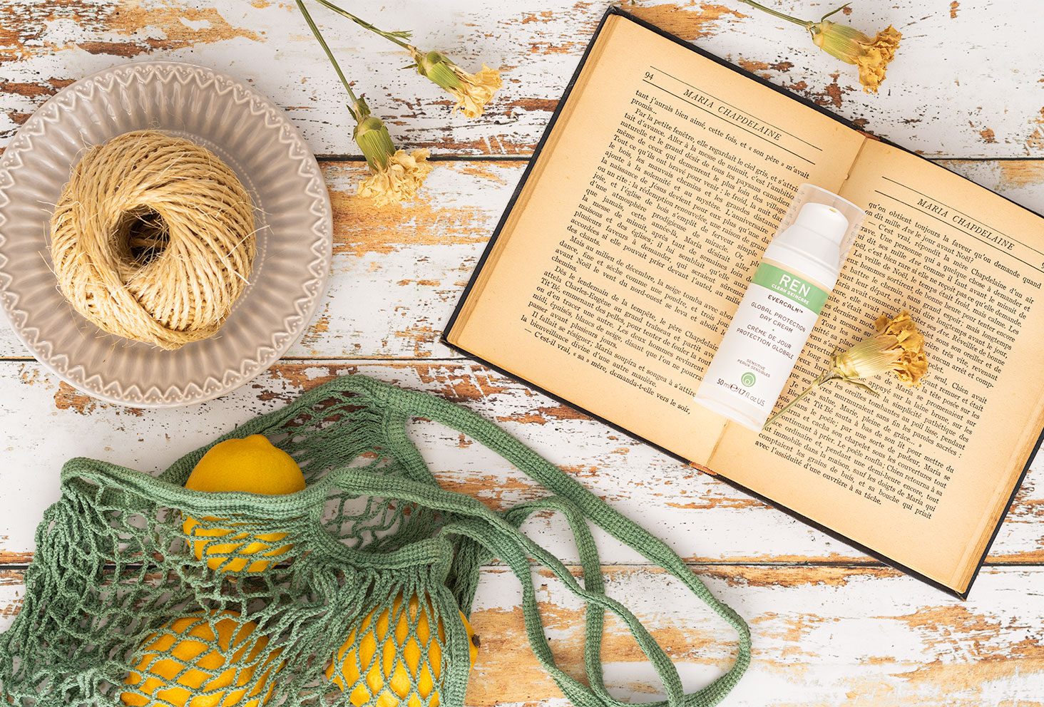 La crème de jour de Ren Clean Skincare posée sur un livre ancien au milieu de citron et de ficelle