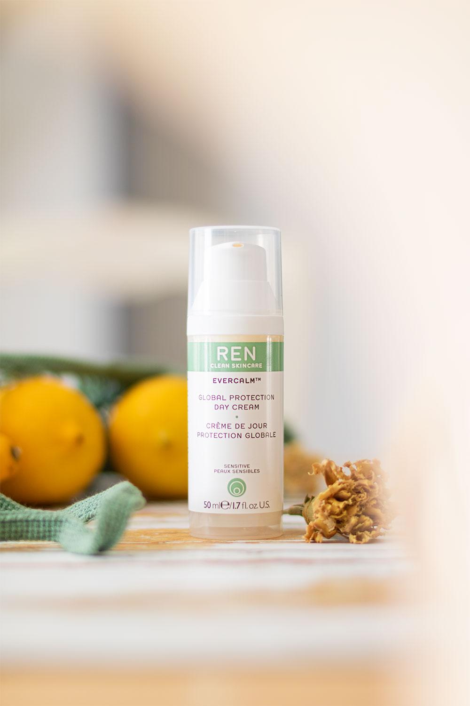 Le soin de jour de Ren Clean Skincare posé sur une table au milieu de citrons et de fleurs séchées