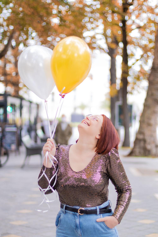 Shooting photo avec des ballons pour un anniversaire, dans la rue en body à paillettes, avec le sourire