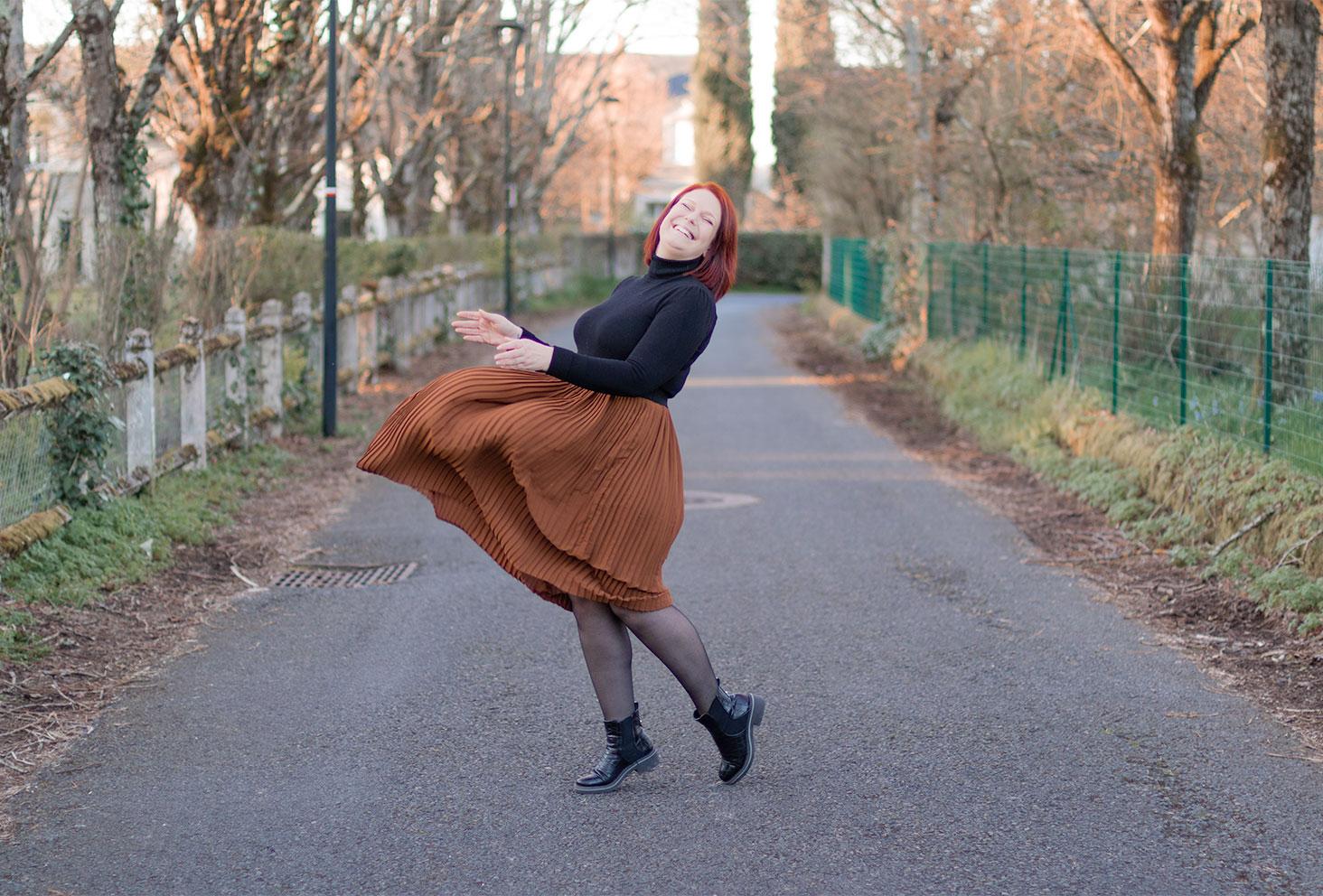 Jupe midi volante marron portée avec un pull moulant à col roulé noir, des collant fin et des bottines noires effet croco