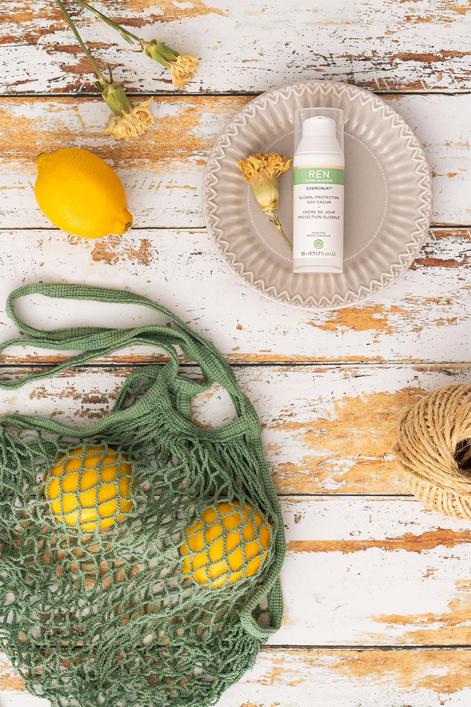 La crème de jour de Ren Clean Skincare posée dans une assiette sur une table en bois au milieu de citron