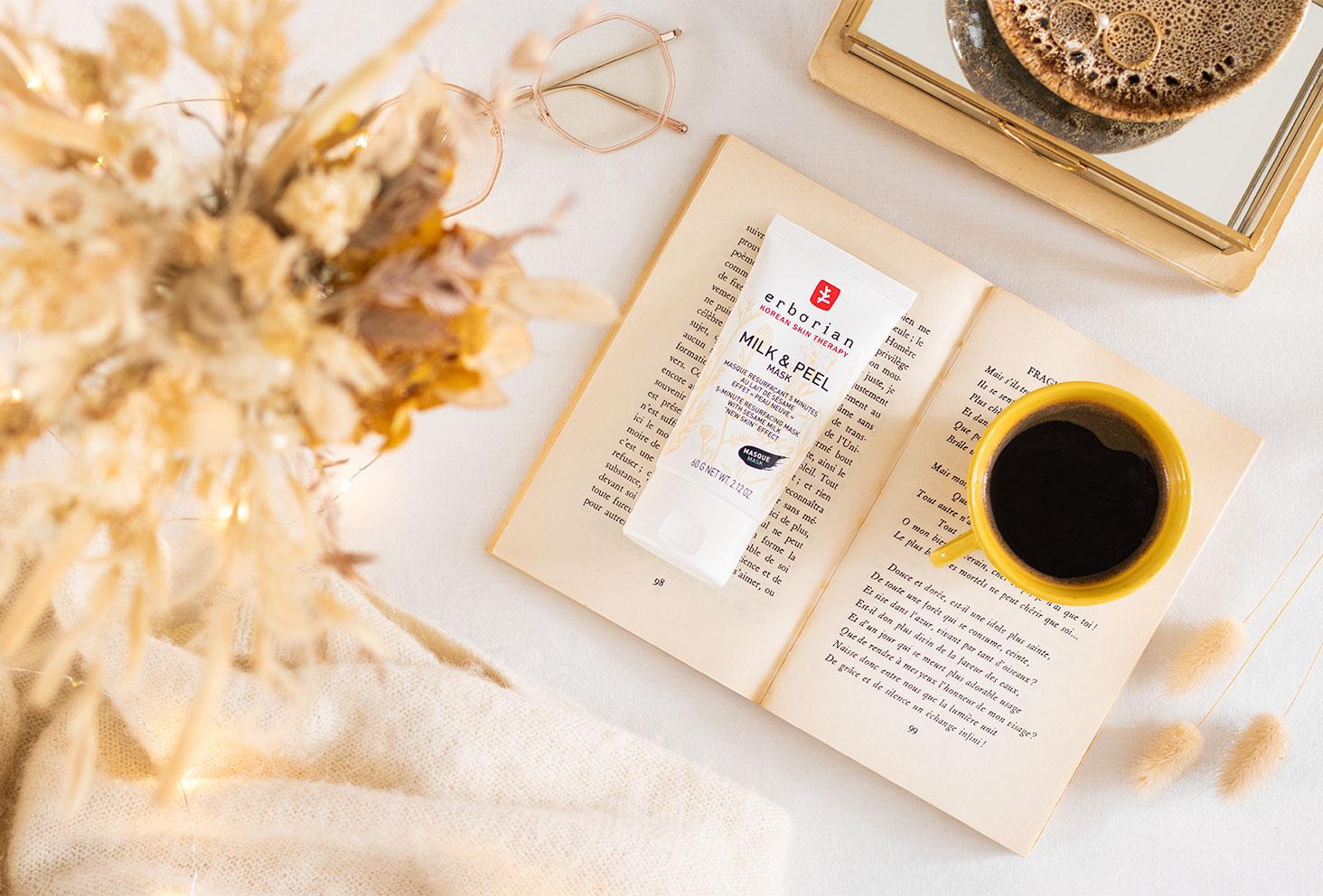 Le masque blanc Milk & Peel au sésame de la marque Erborian, posé sur un livre vintage ouvert avec une tasse de café, sur un drap blanc avec des bijoux et des fleurs séchées
