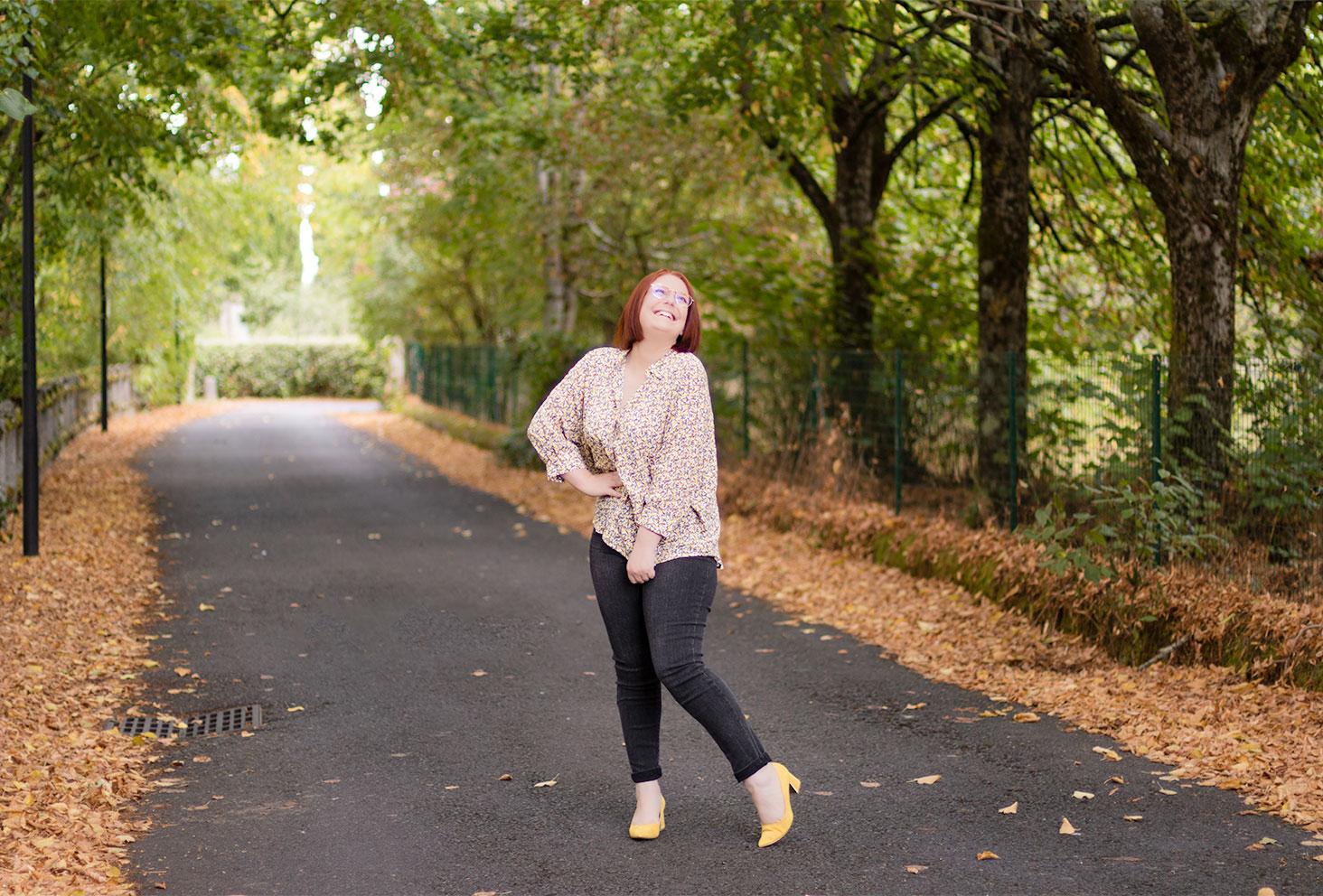 Look Bréal avec une chemise jaune à fleurs et un jean taille très haute, accessoirisée d'escarpins jaunes