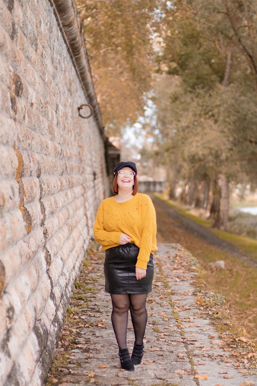 Le pull jaune Bréal porté avec une jupe en simili cuir noir, accessoirisé par une casquette noire et des bottines cloutées noires Bréal, sur les bords de la Loire