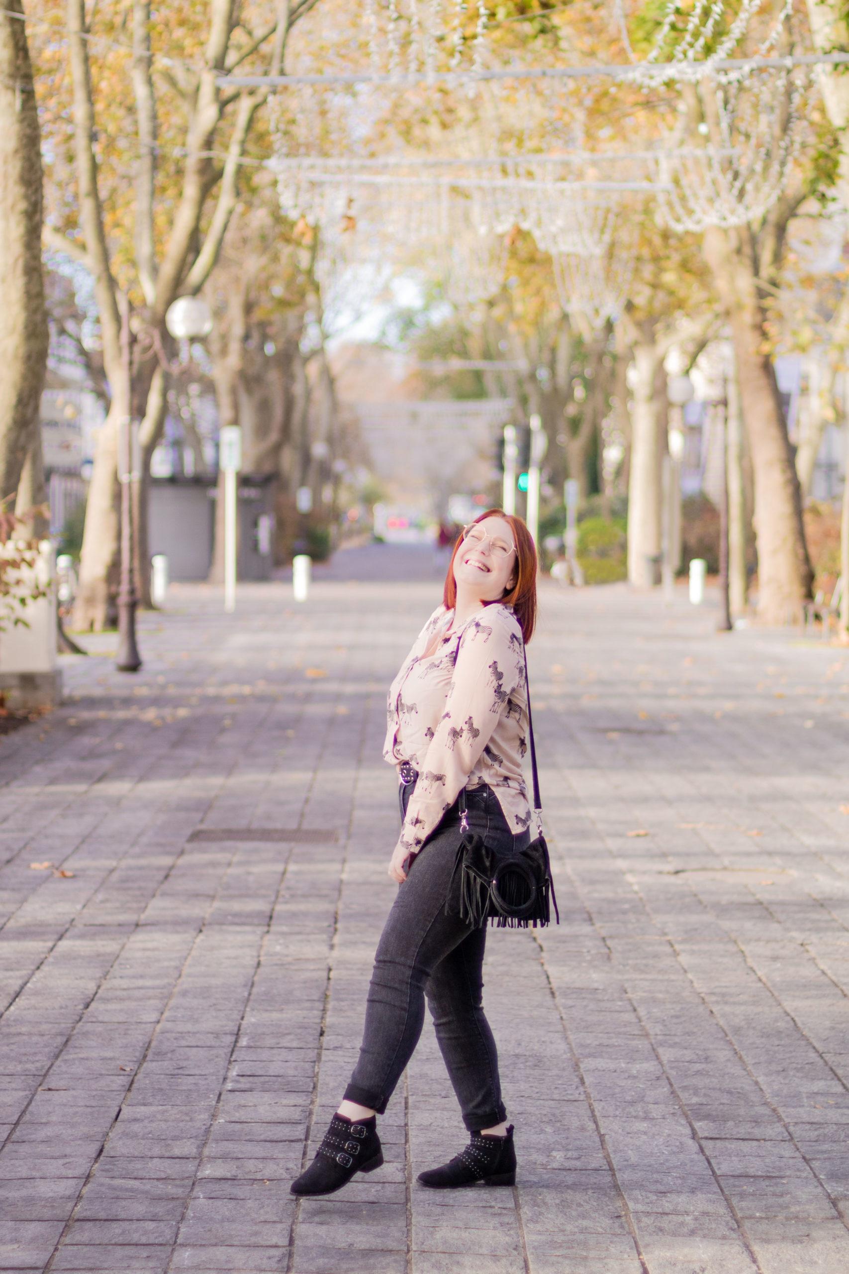 Total look Bréal composé d'une chemise aux motifs zèbres, un jean noir taille très haute, un sac bandoulière à franges noir, et des boots noires cloutées, au milieu du boulevard de Tours