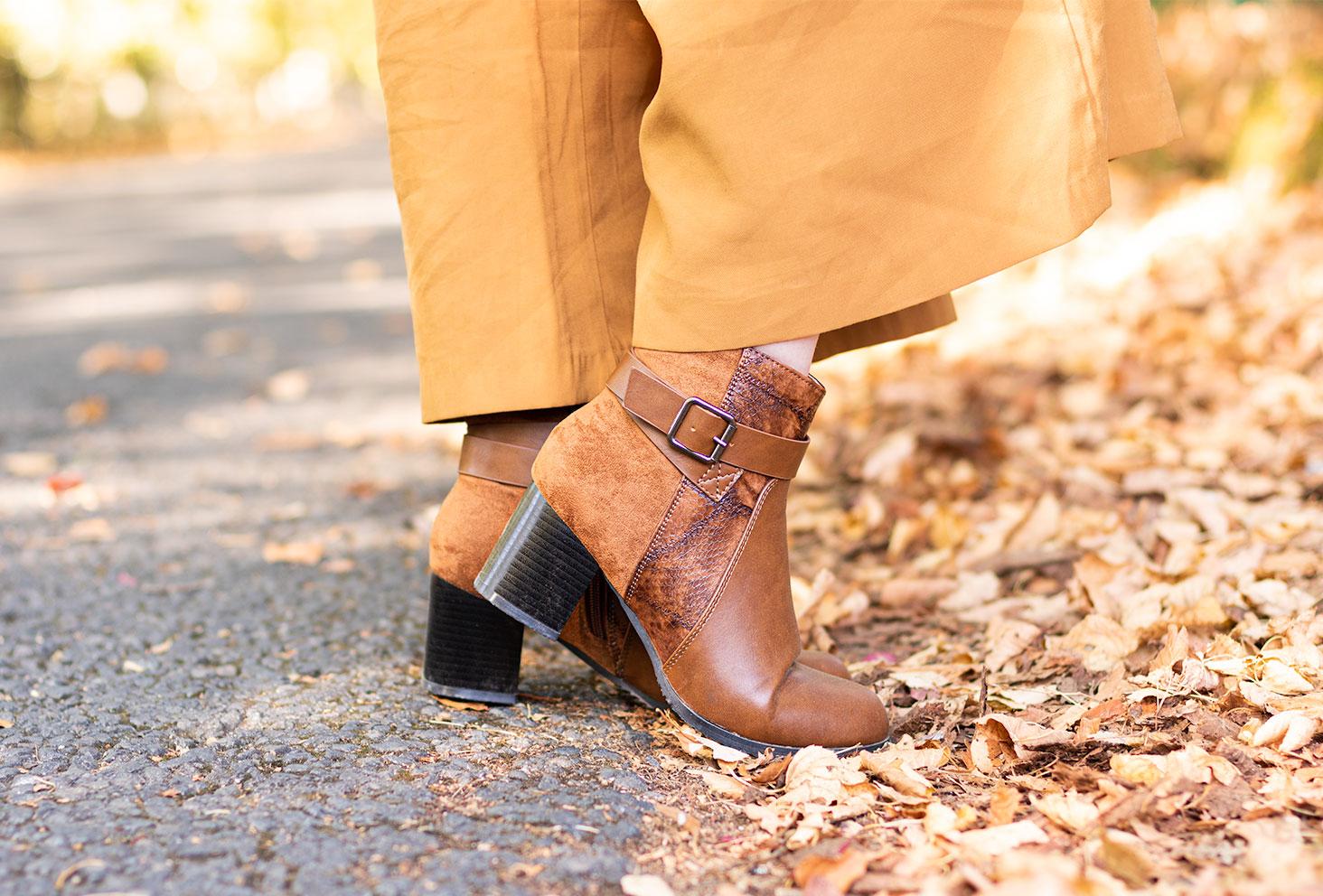Zoom sur les bottines camel à talons et effet croco Bréal, portées avec un pantalon large marron dans les feuilles d'automne