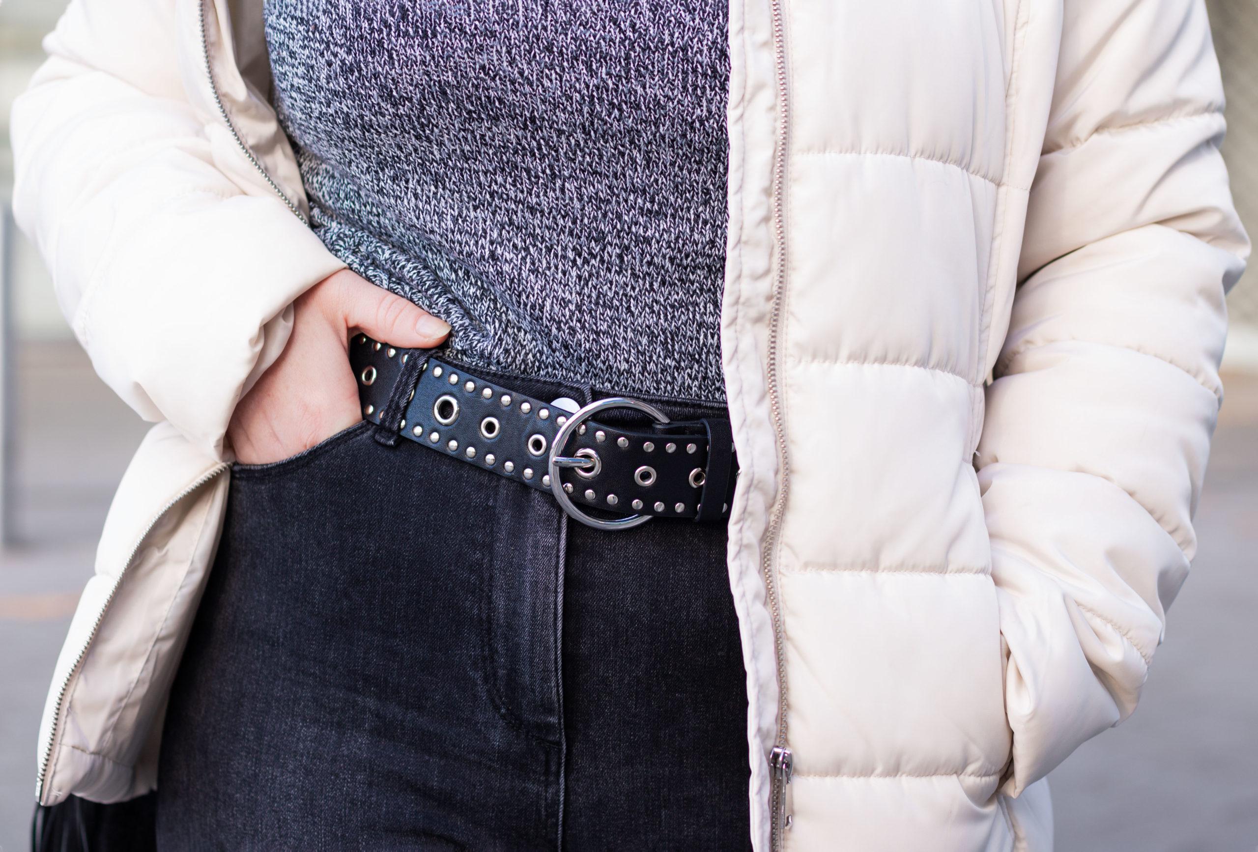 Zoom sur la ceinture noire à oeillets Bréal portée sur un jean noir