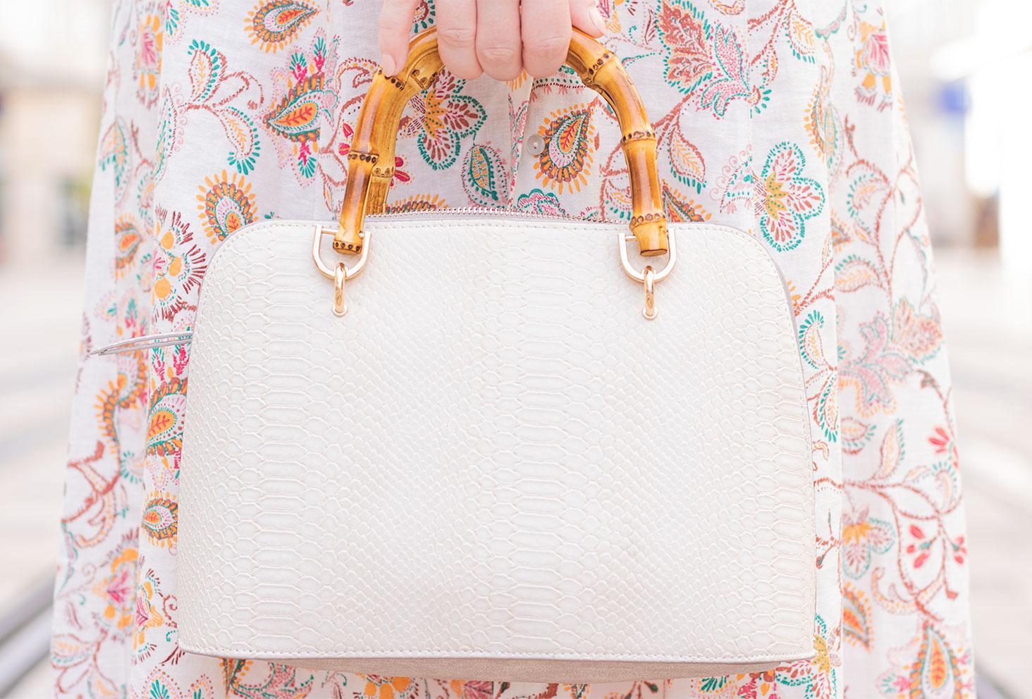 Zoom sur le sac beige aux hanses en bambou Bréal porté