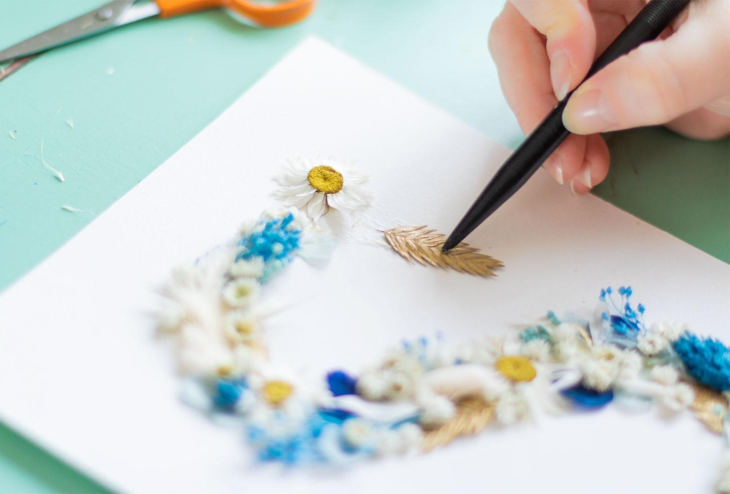 Remplissage de la fin de la lettre S avec une fleurs séchées dorée