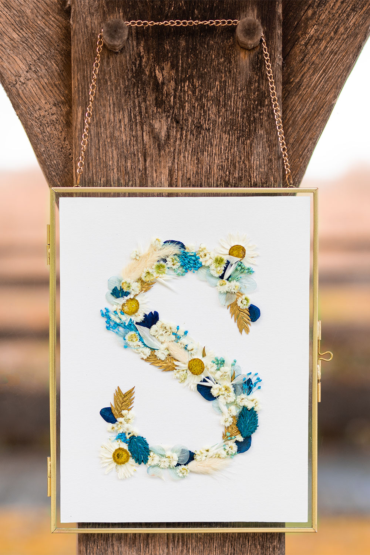 Le cadre de fleurs séchées accroché sur une poutre en bois