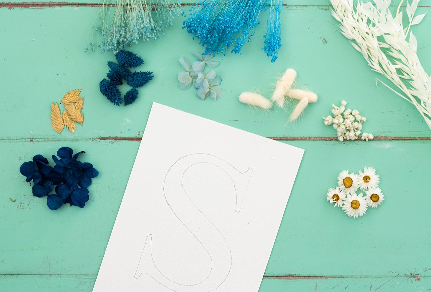 La lettre S sur du papier à dessin blanc à grain, posée sur une table en bois verte, au milieu de fleurs séchées avant de commencer le DIY