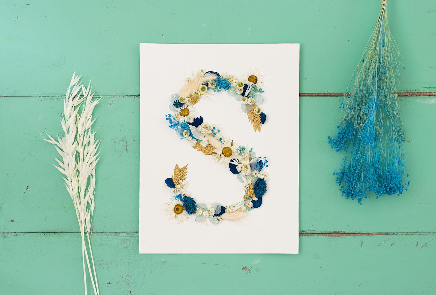 Zoom sur le S en fleurs séchées réalisé à la main sur une feuille à dessin