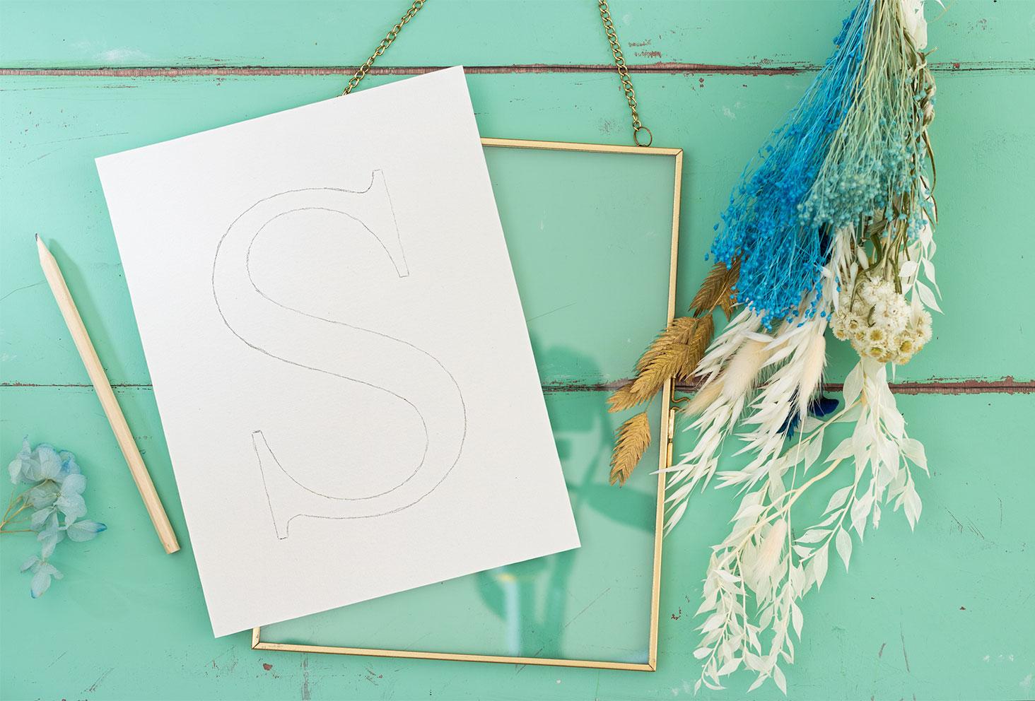 La lettre S sur du papier dessin posé sur un cadre doré avec des fleurs séchées, pour un DIY en fleurs