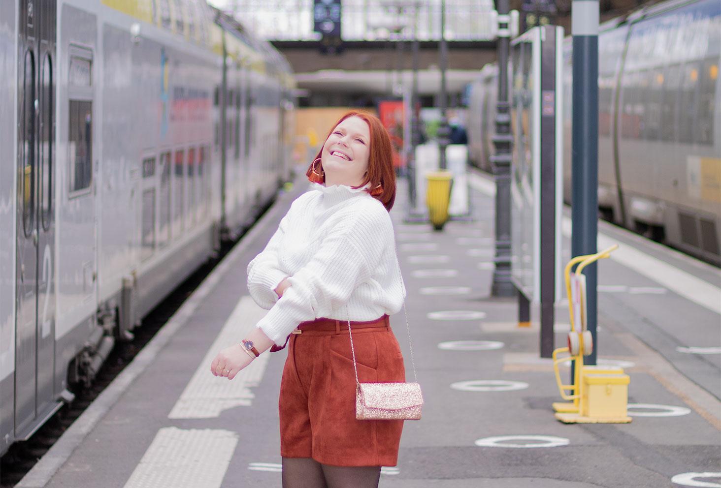 En attendant le train, en look de fêtes à paillettes, avec le sourire