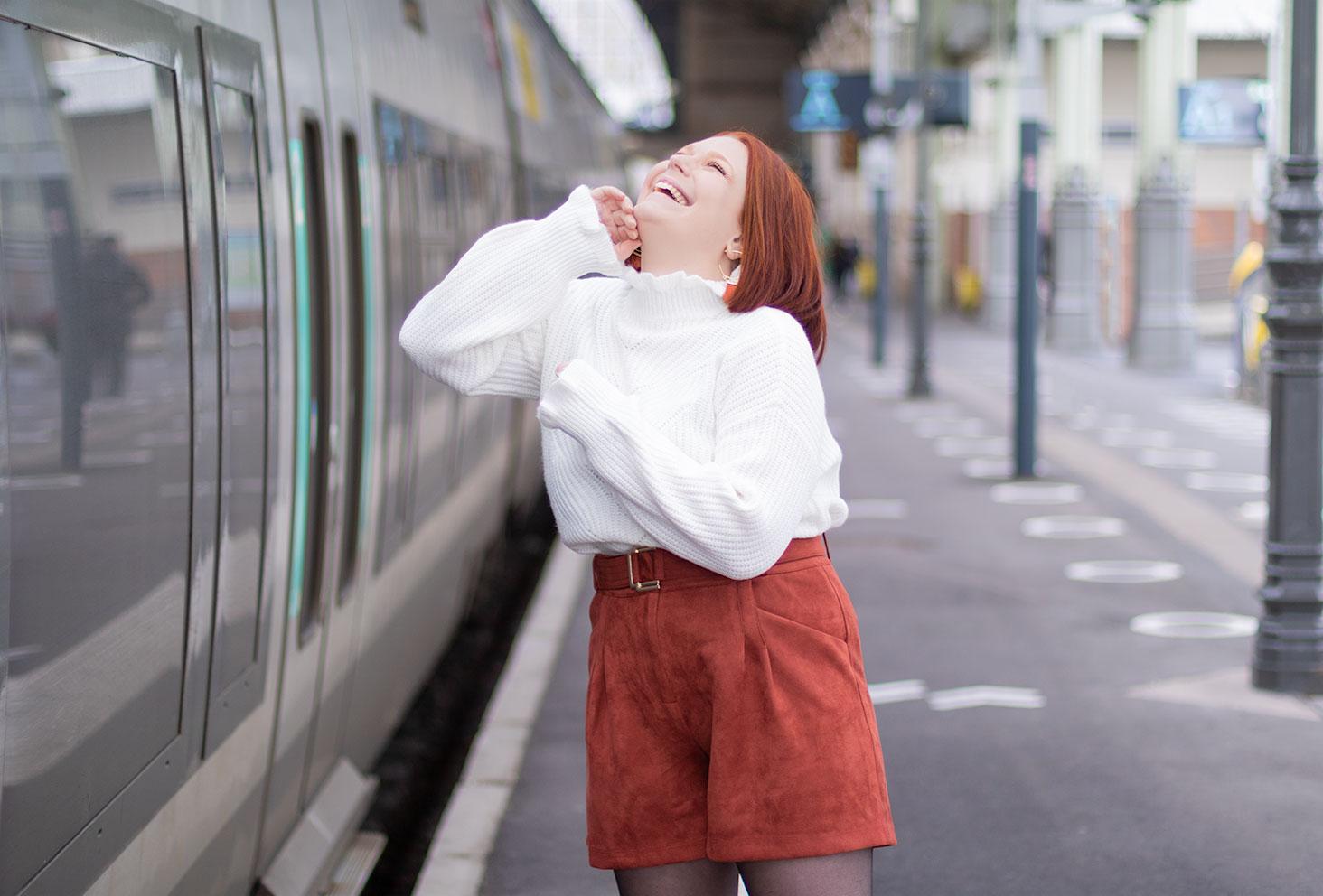 Zoom sur le pull blanc à col froncé et le short en velours, avec le sourire le long d'un train, pour fêter les 5 ans du blog